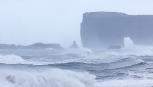 Rocky cliff and icy ocean on a foggy day