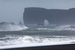 Waves crashing against a rocky, foggy coast
