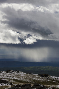 Sunlight and rain over a snowy valley