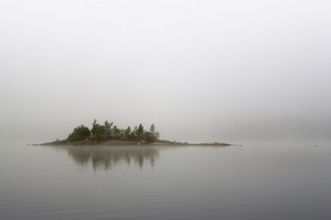 Small island on a foggy lake
