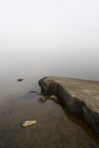 Rocky lake in thick fog