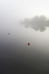 Orange buoys on a lake in thick fog