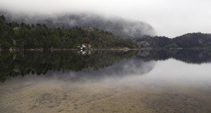 Cottage reflected on a foggy lake