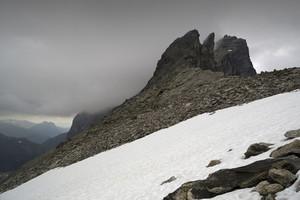 rochas cobertas de neve e um penhasco sob as nuvens