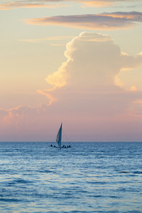 Sailboat in the ocean at sunset