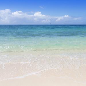 Blue sailboat on the ocean near a white sand beach
