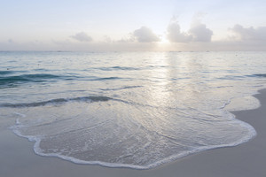 Gentle waves on a tropical beach at sunrise