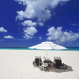 Beach chairs under an umbrella on a white sand beach