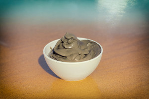 Dead Sea mud for spa treatments in a cup on the beach