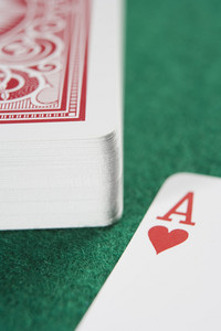 Deck of cards on green baize with ace of hearts