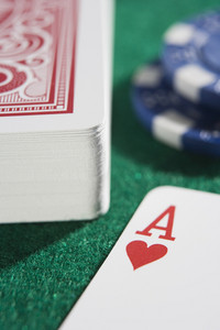 Deck of cards with ace of hearts on green baize