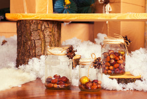 Decoration from glass jars with acorns and chestnuts and synthetic snow in front of the bench
