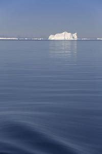 Deep blue ocean and a distant iceberg