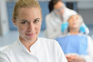 Dental assistant closeup looking camera professional dentist checkup patient woman