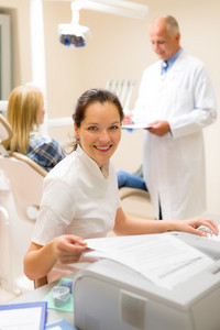 Dental assistant smiling woman prepare patient documentation stomatology clinic