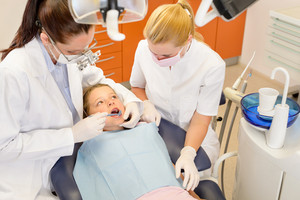 Dental assistant with dentist female and little child at stomatology surgery