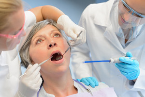 Dental check elderly woman patient professional dentist team open mouth