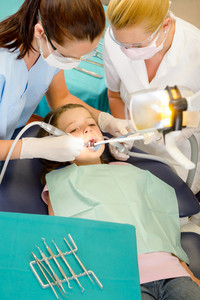 Dentist and assistant with little girl patient  at stomatology clinic