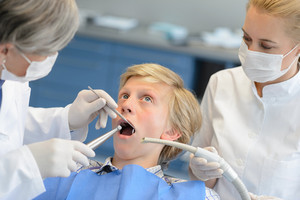 Dentist and assistant with scared teenage patient open mouth checkup