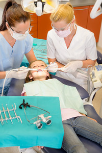 Dentist and nurse doing operation on child patient