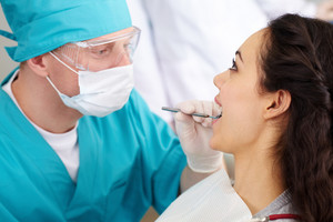 Dentist in protective glasses carrying out a dental check-up
