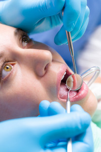 Dentist surgery closeup of woman's open mouth with dental tools