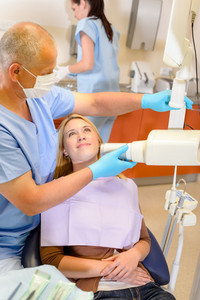 Dentist taking x-ray of female patient with nurse assistance