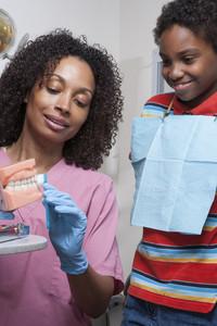 Dentist teaching patient to brush teeth