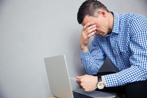 Depressed man holding credit card