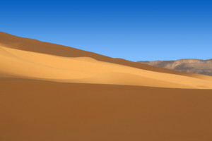 Desert sand dunes under a clear blue sky