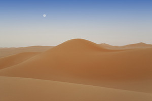 Desert sand dunes under a full moon at dusk