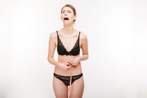 Despairing crying young woman in black lingerie standing and measuring her waist