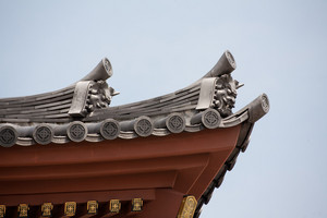 Detail on japanese temple roof against blue sky.