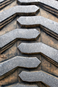Detail up close of a tire tread from a tractor or other heavy duty construction machinery.
