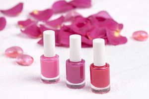 Different shades of rose nail polish on white towel decorated with rose petals