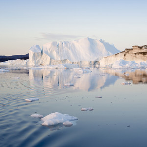 Dirt-streaked iceberg and ice floes along the coast at dawn
