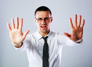 Dissatisfied businessman gesturing stop sign with both hands on gray background