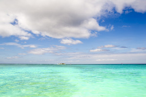 Distant boat on clear, tropical waters