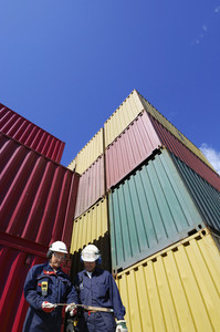 dock workers with stacks of shipping containers