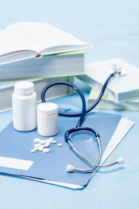 Doctor accessories with medical pills on blue background