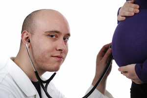 Doctor concentrating on pregnancy examination with stethoscope