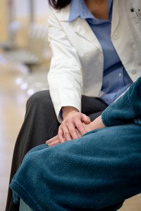 Doctor holding senior patient hands in hospital