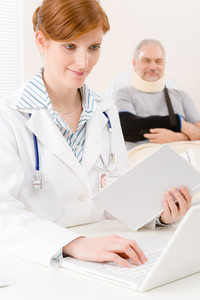 Doctor office - portrait female physician look up book senior patient