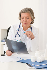 Doctor office - senior female physician hold x-ray sit behind desk