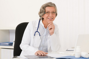 Doctor office - senior female physician sit behind desk smiling