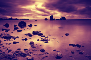 Dramatic cloudy sky before sunrise over a rocky seashore