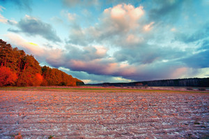 Dramatic sunset at field covered with first snow