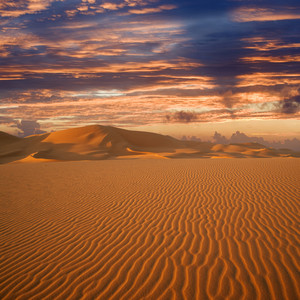 Dramatic sunset over a vast, sandy desert