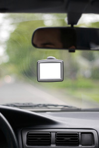 Driver using a portable gps unit that is mounted to the windshield.  The blank screen includes clipping path.