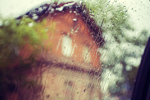Driving in rain. Focus on raindrops on the window